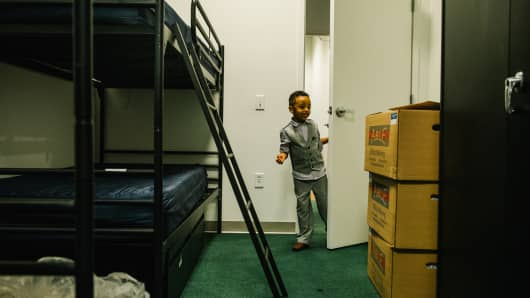 Mikias Aiychew examines his new room at the Carpenter's Shelter in an abandoned Macy's department store, at Landmark Mall in Alexandria, Va., June 9, 2018.