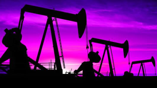 Oil derricks pump oil in a field in North Dakota.
