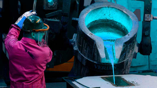 An employee pours molten steel into a casting for a church bell at the Verdin Corp. production facility in Cincinnati, Ohio.