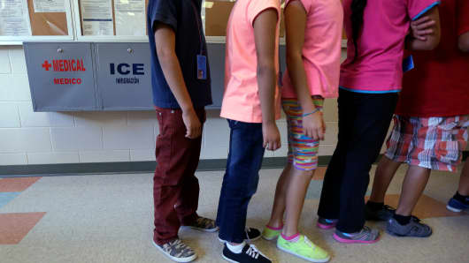 In this Sept. 10, 2014 file photo, detained immigrant children line up in the cafeteria at the Karnes County Residential Center, a temporary home for immigrant women and children detained at the border, in Karnes City, Texas.