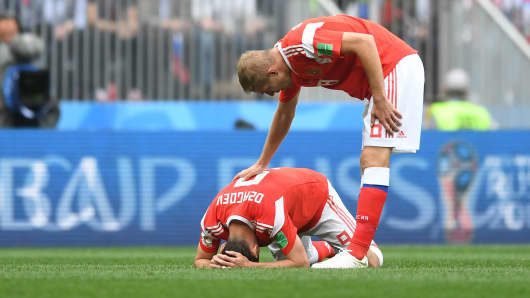 Iury Gazinsky of Russia checks on teammate Alan Dzagoev of Russia as he goes down injured during the 2018 FIFA World Cup Russia Group A match between Russia and Saudi Arabia at Luzhniki Stadium on June 14, 2018 in Moscow, Russia.