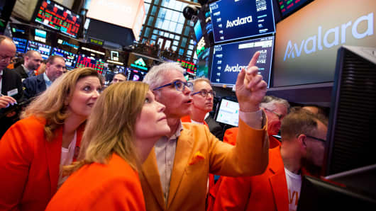 Scott McFarlane, chief executive officer of Avalara Inc., center, points to a monitor during the company's initial public offering (IPO) on the floor of the New York Stock Exchange (NYSE) in New York, U.S., on Friday, June 15, 2018.