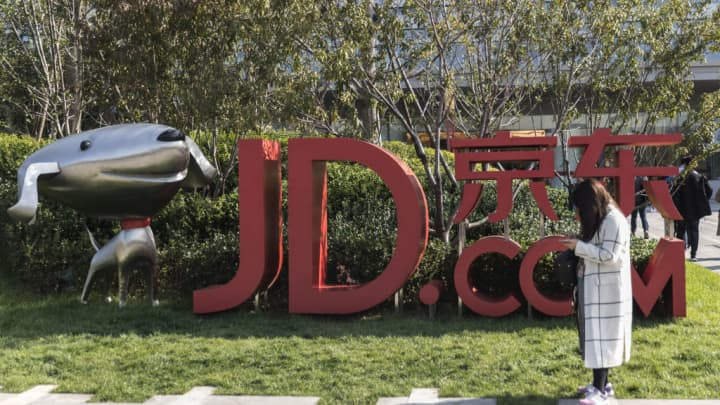 A woman stands next to signage incorporating the logo of JD.com, and the company's mascot 'Joy,' at the company's headquarters in Beijing, China.