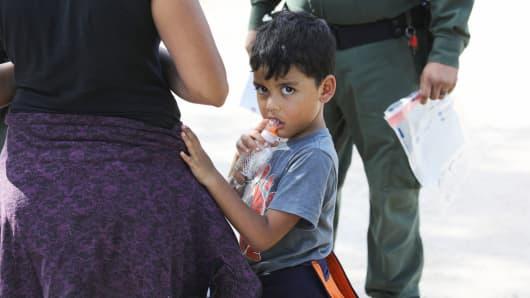 Central American asylum seekers wait as U.S. Border Patrol agents take them into custody on June 12, 2018 near McAllen, Texas.