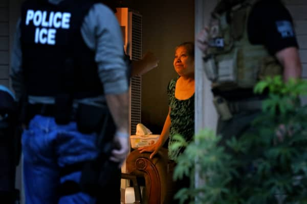 ICE officers in search of a man question his mother about his whereabouts in a morning raid on his r