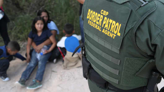 Central American asylum seekers wait as U.S. Border Patrol agents take them into custody on June 12, 2018 near McAllen, Texas.