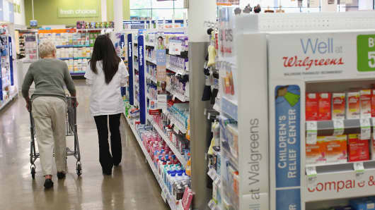 A pharmacist helps a customer at a Walgreens pharmacy in Wheeling, Illinois.
