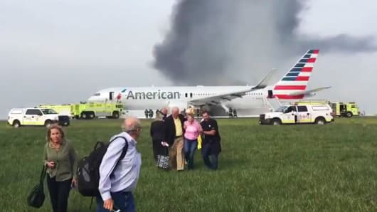 In this photo provided by passenger Jose Castillo, fellow passengers walk away from a burning American Airlines jet that aborted takeoff and caught fire on the runway at Chicago's O'Hare International Airport on Friday, Oct. 28, 2016.