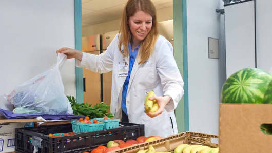Dietitian Anna Ziegler selects fresh produce for a Fresh Food Farmacy patient.