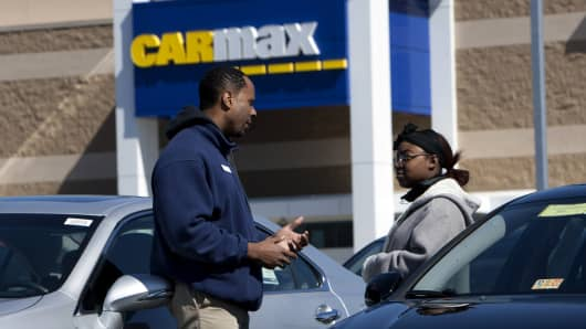 Sales consultant Jomo Wilson, left, speaks to a potential buyer on the lot at a CarMax dealership in Brandywine, Maryland.