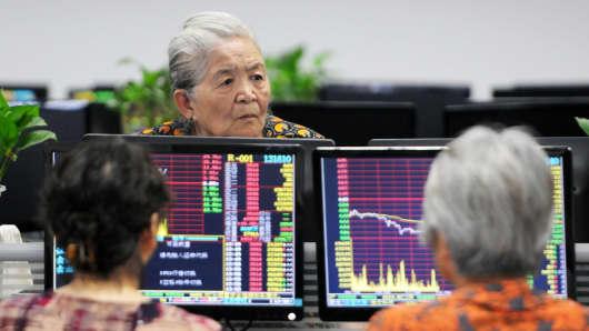 Investors monitor stock prices at a securities company in Jiujiang, China, June 19, 2018.