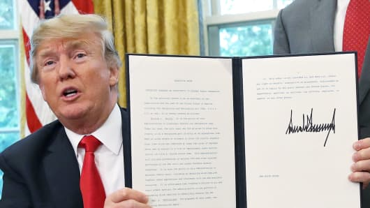 President Donald Trump displays an executive order he signed that will end the practice of separating family members who are apprehended while illegally entering the United States on June 20, 2018 in Washington, DC.