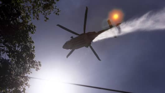A water-dropping helicopter trails mist as as firefighters clear burned and unburned brush from a hillside after a wildfire broke out in the Benedict Canyon area of Los Angeles, June 12, 2018.