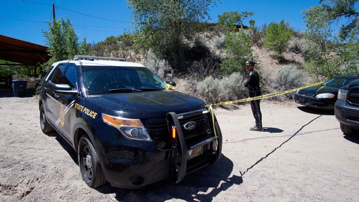 New Mexico State Police officers investigate a triple homicide in Dixon on May 31, 2018.