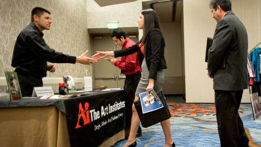 A recruiter for The Art Institutes, left, greets a job seeker at a National Career Fairs job fair in San Diego.
