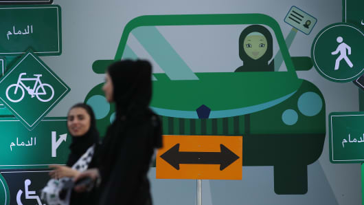 Young women wearing the traditional abaya walk past a sign as they help to organize an outdoor educational driving event for women on June 21, 2018 in Jeddah, Saudi Arabia.