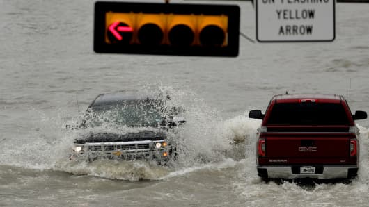 A truck is hit by the wake of another as they navigate a road that flooded after the area received several inches of rain, Wednesday, June 20, 2018, in Weslaco, Texas.