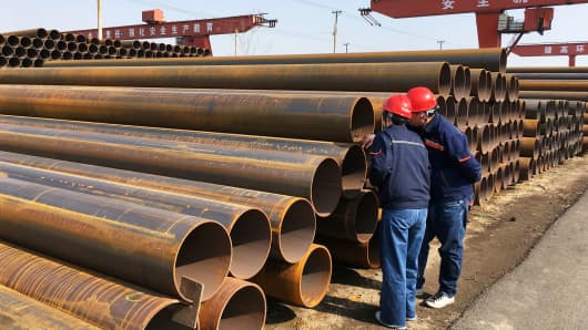 Workers inspect steel pipes at a steel mill of Hebei Huayang Steel Pipe Co in Cangzhou, China last March.