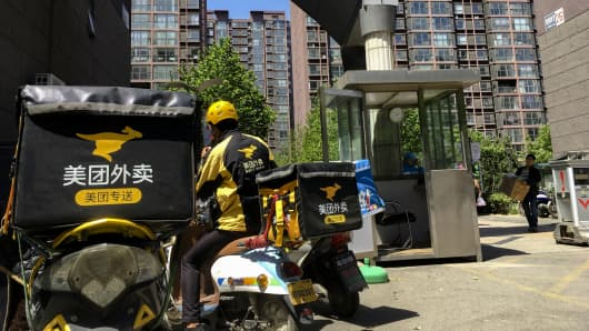 Motorcycles for the take-out delivery service of Meituan.com, stop outside a Beijing residential district.