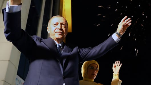 President of Turkey Tayyip Erdogan (L) and his wife Emine Erdogan (R) greet the crowd from the balcony of the ruling AK Party's headquarters as fireworks illuminate the sky following his election success in presidential and parliamentary elections in Ankara, Turkey on June 25, 2018.
