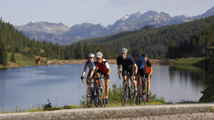 A group of five cyclists ride past a lake at the crest of a Vail pass near Vail, Colorado.