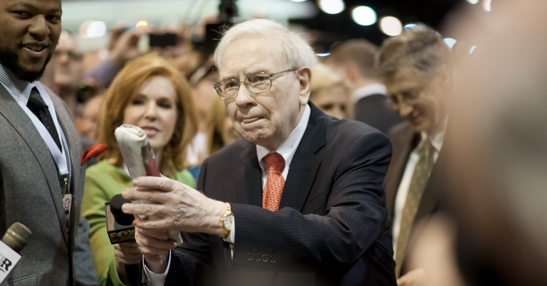 Warren Buffett, chairman and chief executive officer of Berkshire Hathaway Inc., prepares to throw a newspaper as he tours the exhibition floor prior to the start of the Berkshire shareholders meeting on Saturday, May 4, 2013.
