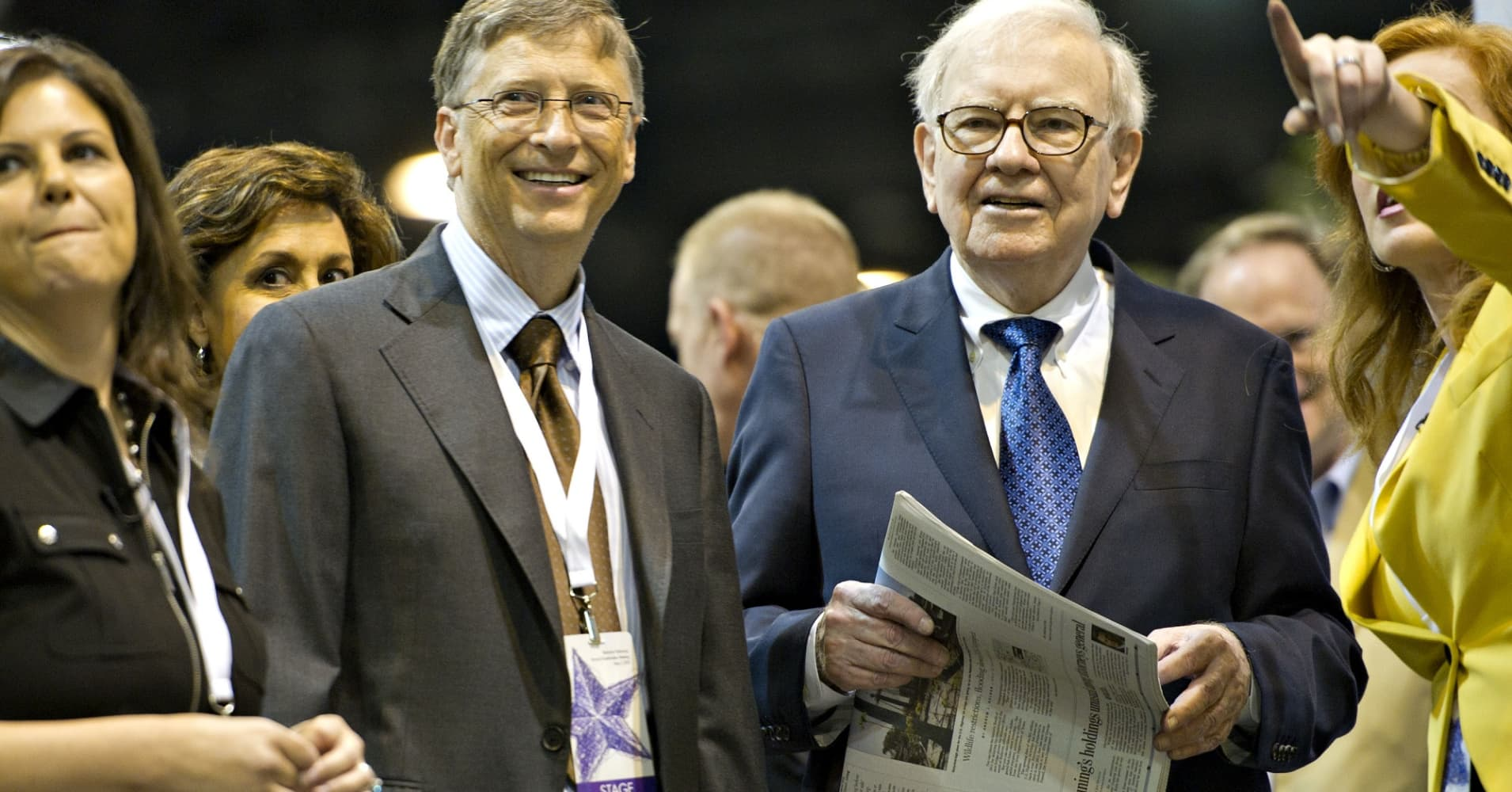 Warren Buffett, chairman of Berkshire Hathaway Inc., right, and Bill Gates, chairman and co-founder of Microsoft Corp., participate in a newspaper toss event at the Berkshire Hathaway annual shareholders meeting on Saturday, May 5, 2012.