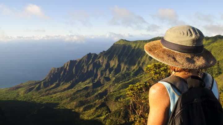 A woman in her fifties looking at the dramatic landscape at Kalalau Lookout on Kauai
