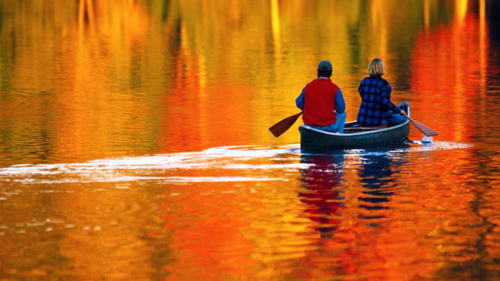 COUPLE CANOEING ON LAKE IN AUTUMN