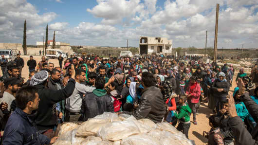 Thousands of people displaced from Afrin line up to receive bread in the village of Fafin, South of Tall Rafat on March 25, 2018.