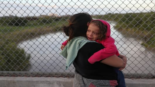 After being denied entry by U.S. Customs and Border Protection officers, an asylum seeking Honduran mother holds her crying 3-year-old daughter on the Mexican side of the Brownsville & Matamoros International Bridge near Brownsville, Texas, U.S., June 24, 2018.