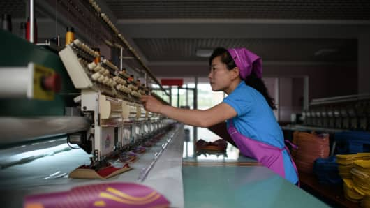An employee of the Ryo Won Footwear Factory operating a machine making shoe parts in Pyongyang, North Korea.