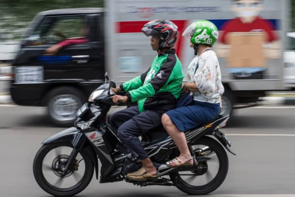 A passenger takes a ride on a Go-Jek motorcycle taxi in Jakarta on May 24, 2018.