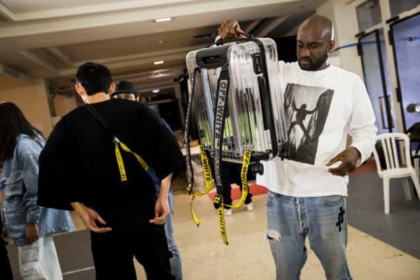 Designer Virgil Abloh with an Off-White x Rimowa suitcase at Paris Fashion Week in June 2018