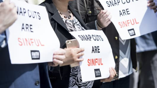 Faith activists hold signs during a news conference with faith leaders to 'urge lawmakers to reject proposed cuts to the Supplemental Nutrition Assistance Program (SNAP) in the Farm Bill' on Monday, May 7, 2018.