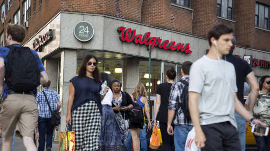 Pedestrians walk past a Walgreens store in New York.