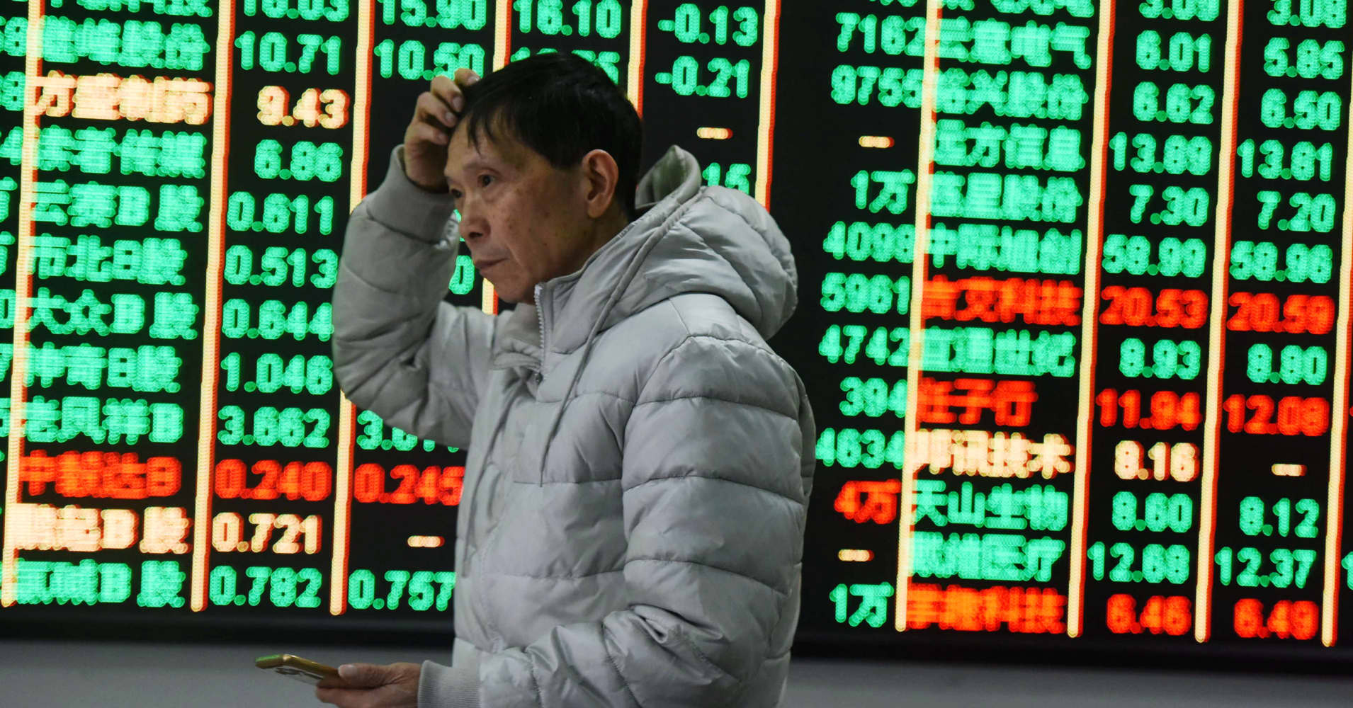 An investor watches the electronic board at a stock exchange hall in Hangzhou, China.