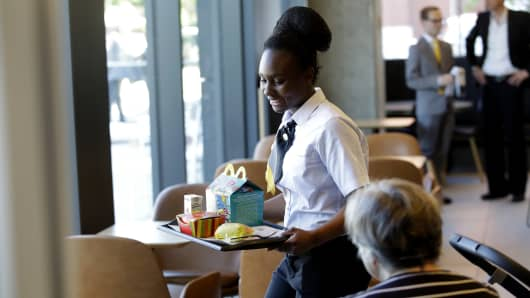 An employee brings an order to customers at the restaurant inside the new McDonald's Corp. headquarters in Chicago, Illinois, U.S., on Monday, June 4, 2018.