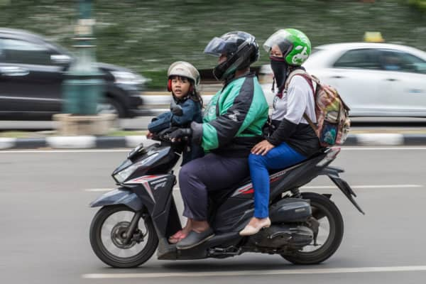 A Go-Jek motorcycle taxi rider ferries passengers in Jakarta on May 24, 2018.