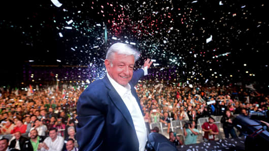 Newly elected Mexico's President Andres Manuel Lopez Obrador (C), running for 'Juntos haremos historia' party, cheers his supporters at the Zocalo Square after winning general elections, in Mexico City, on July 1, 2018.