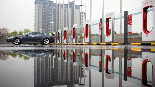 Zang Yi charges her Tesla car at a charging point in Beijing, China, April 13, 2018.