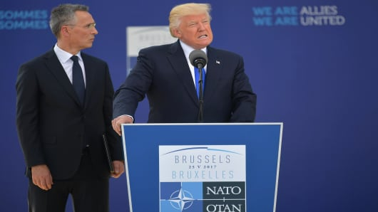 US President Donald Trump (C) delivers a speech next to NATO Secretary General Jens Stoltenberg (L) during the unveiling ceremony of the Berlin Wall monument, during the NATO (North Atlantic Treaty Organization) summit at the NATO headquarters, in Brussels, on May 25, 2017.