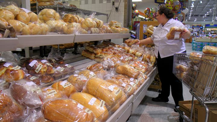 A woman stocking up bread in Publix, grocery store.