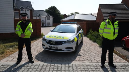 Police officers are seen standing guard outside a residential address in Amesbury, southern England, on July 5, 2018 where police reported a man and woman were found unconscious in circumstances that sparked a major incident after contact with what was later identified as the nerve agent Novichok.