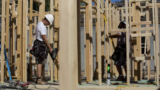 Contractors work on the frame of a home under construction at the D.R. Horton Express Homes Magma Ranch housing development in Florence, Arizona.