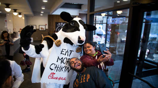 Attendees take a selfie photograph with the Chick-fil-A mascot during an event ahead of the grand opening for the restaurant in New York.