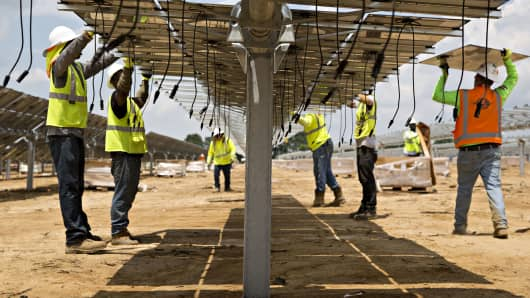 Workers mount solar panel modules during construction of a Silicon Ranch Corp. solar generating facility in Milligan, Tennessee.
