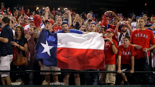 Fans of the Texas Rangers hold a Texas state flag at a game in Arlington, Texas.