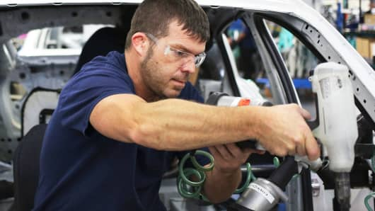 An employee installed at the BMW assembly plant in Greer, South Carolina, interior in a BMW X4 sports car on the assembly line.