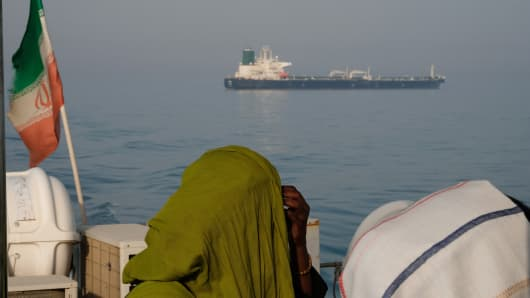 Foreign tourists in veils seen on a passenger boat with the Iranian flag amass in the waters of the Strait of Hormuz on May 2, 2017 near Hormuz Island, Iran. An oil tanker is seen on the move in the background.